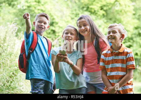 Group Of Children Geocaching In Woods - Stock Image