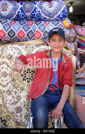 Portrait of an Iranian boy with a stack of carpets and textiles. Shiraz, Iran - Stock Image
