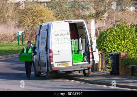 A woman driver delivering waitrose shopping goods from a van, uk - Stock Image