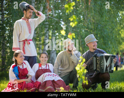 People in traditional Russian clothes sit on the lawn - one of them plays the accordion - gorizontal view - Stock Image