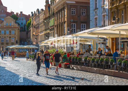 Poznan Market Square, view of people walking past a street cafe in the Market Square (Stary Rynek) in Poznan Old Town, Poland. - Stock Image