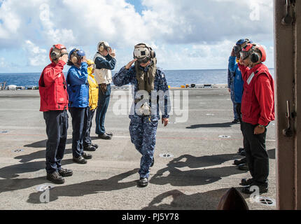 180827-N-RI884-0017 PACIFIC OCEAN (Aug. 27, 2018) Japan Maritime Self-Defense Force (JMSDF) Rear Admiral. Tsutomu Shirane, the commander of the JMSDF Mine Warfare Force, salutes sideboys upon arriving aboard the amphibious assault ship USS Wasp (LHD 1), as part of a visit off the coast of Okinawa, Japan. The Wasp Amphibious Ready Group is currently operating in the region to enhance interoperability with partners and serve as a ready-response force for any type of contingency. (U.S. Navy photo by Mass Communication Specialist 1st Class Daniel Barker/Released) - Stock Image