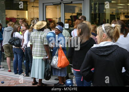 Older black ladies and younger white women queuing outside Primark, Derby, UK - Stock Image