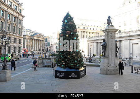 Fortnum & Mason Christmas tree outside the Royal Exchange and Bank of England with a street view of Mansion House City of London UK  KATHY DEWITT - Stock Image
