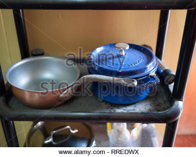 An expat's collection of imported cookware sits on plastic shelving. - Stock Image