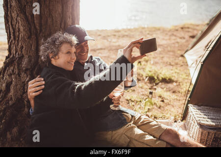 Shot of a senior couple taking a photo of themselves while outside a tent. Mature couple camping near a lake taking - Stock Image