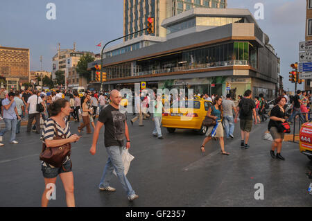 Pedestrians and taxis on Taksim square in central Istanbul.    This is a partial view of the square, on its side - Stock Image