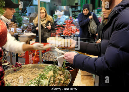 An Italian chef handing a customer a food carton with hot wild mushroom spelt risotto cooking at a Borough Market stall London England UK KATHY DEWITT - Stock Image