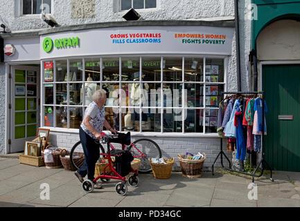 Senior woman outside Oxfam charity shop, England UK - Stock Image