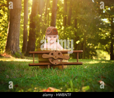 A little baby is sitting in a wooden airplane basket prop in the park pretending to travel and fly with a pilot - Stock Image