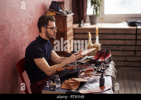 master painting the insoles of clients, side view photo, hobby, designing shoes - Stock Image