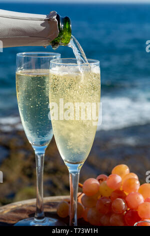 Waiter pouring Champagne, prosecco or cava in two glasses on outside terrace with sea view  close up - Stock Image