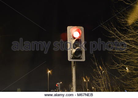 Traffic signal with red light on covered in snow at night in the dark - Stock Image