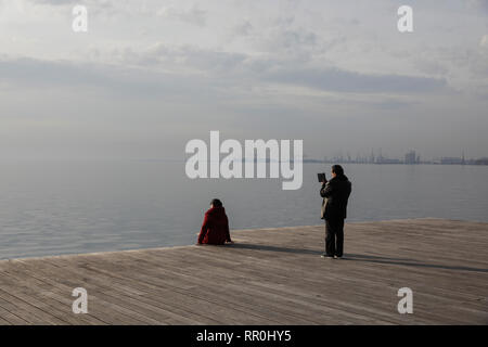 An Asian tourist take a photo his wife at the seafront promenade of Thessaloniki, Greece on January 18, 2019. - Stock Image