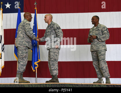 Gen. CQ Brown, Jr., Pacific Air Forces commander, left, coins Tech. Sgt. Juan Martinez-Gomez, 51st Maintenance Group load barn NCO in charge, during an all call at Osan Air Base, Republic of Korea, Aug. 29, 2018. Martinez-Gomez received a coin for his dedication to the weapons flight, training 150 weapons Airmen, and being a leader among his peers. (U.S. Air Force photo by Staff Sgt. Sergio A. Gamboa) - Stock Image