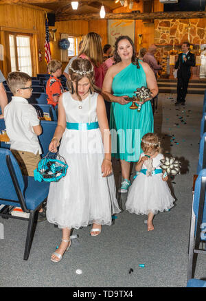Flower girls walking aisle after wedding ceremony; Congressional Church; Buena Vista; Colorado; USA - Stock Image