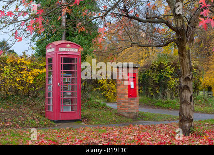 a red telephone and letterbox on a colourful autumn day in Shackleford, near Godalming, Surrey, England - Stock Image