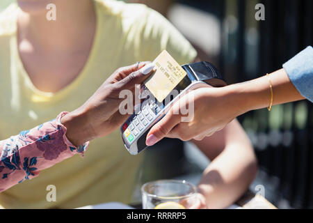 Woman paying waitress with smart card - Stock Image