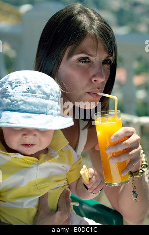 Mother and Toddler outdoors, mother dinking orange juice, child holding a biscuit, food crumbs on lips, wearing - Stock Image