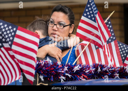 Anchorage, Alaska. 4th July, 2018. A child rests in his mothers arms lost in American flags during the annual Independence Day parade July 4, 2018 in Anchorage, Alaska. Credit: Planetpix/Alamy Live News - Stock Image
