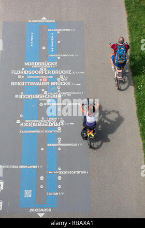 Vienna cycling, rear view of a middle-aged couple riding their bikes on a cycle path on the Danube Island of Donauinsel in Vienna, Wien, Austria. - Stock Image