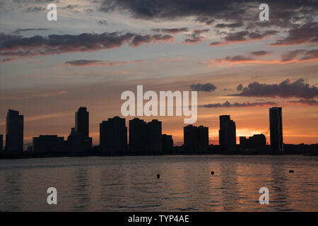 The sun setting over the Hudson River and Jersey City, New Jersey on June 25, 2019. - Stock Image