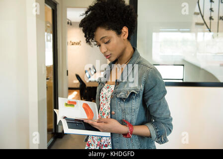 Woman flipping through book - Stock Image
