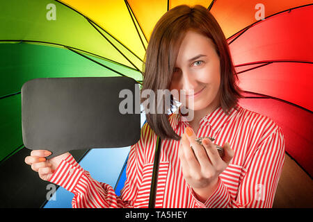 Happy woman on rainbow colored background with watch and empty sign board. - Stock Image