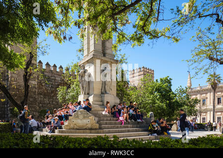 School children having a lunch break, monument to the Immaculate Conception, Plaza del Triunfo, Real Alcazar in background; Seville, Andalusia, Spain - Stock Image