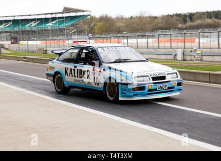A 1989  Ford Sierra RS500  Cosworth, driven by Andy Rouse  and Guy Edwards, in the pit lane at the 2019 Silverstone Classic Media Day. - Stock Image