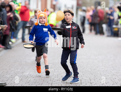 The annual Shrove Tuesday pancake race taking place in Bore Street, Lichfield, England, UK - Stock Image