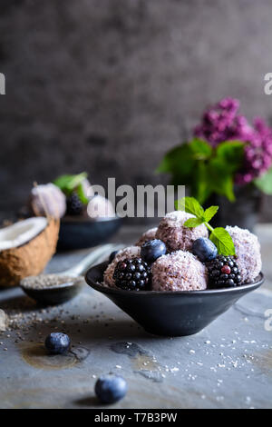 Sweet chia seed balls with blueberry and blackberry puree, coated with grated coconut - Stock Image