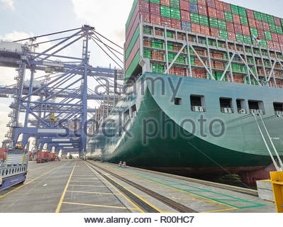 Huge cargo ship with full load waiting to be emptied at dock port - Stock Image