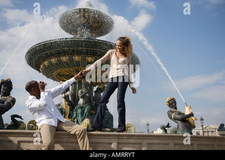 African man taking photograph of girlfriend - Stock Image