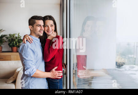 Young couple in love standing by the window at home, hugging. Copy space. - Stock Image