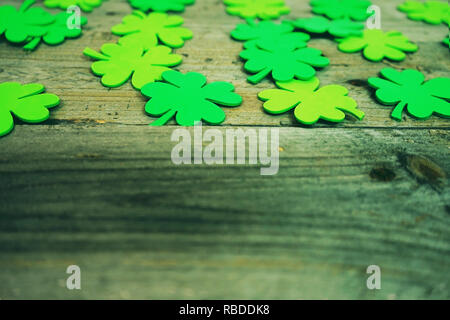 Beautiful close-up of many irish shamrocks, feast clovers, in a row that remind luck or Saint Patrick's Day and wooden tables as background - Stock Image