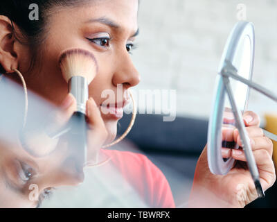 Close-up of female experimenting with make up techniques with blusher, brush and foundation. - Stock Image