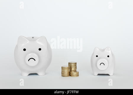 Two unhappy piggy banks, one small, one big, with a pile of coins, copyspace - Stock Image