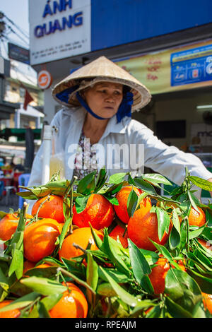 A Vietnamese market stall worker sells fresh oranges in the street. - Stock Image