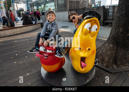 Youung brothers pose for a photo sat on models of two cartoon characters from the Korean cartoon 'Larva'. - Stock Image