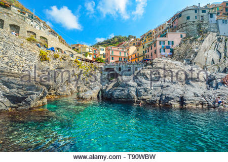 The rocky coastline and swimming bay on the Ligurian Coast of Italy at the village of Manarola, Italy, part of the Cinque Terre, an Unesco site - Stock Image