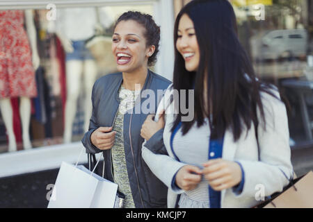 Smiling, happy young women with shopping bags - Stock Image
