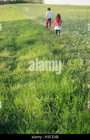 Children walking in field - Stock Image