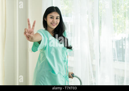 Young Asian patient woman standing at hospital room with walking stick showing victory sign for cheerful. - Stock Image
