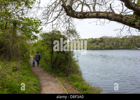 Mother and daughter walking along the Pembrokeshire Coastal Path at Bosherston Lily Ponds. - Stock Image