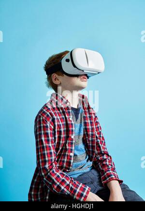 Boy 10yo wearing virtual reality head gear, VR Glasses - Stock Image