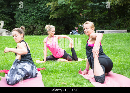 Young women practicing yoga in park - Stock Image
