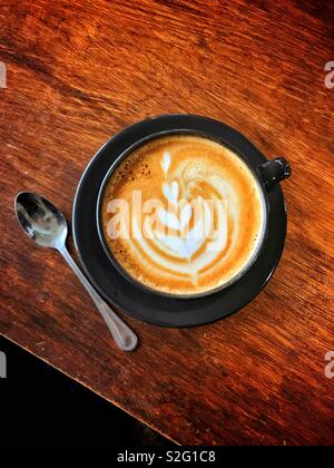 An overhead view of a cup of Latte coffee. Interesting patterns are on the top of the drink. No people, but plenty of space for copy. - Stock Image