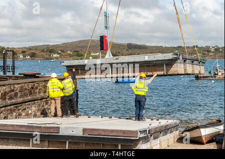 Schull, West Cork, Ireland. 16th Apr, 2019. West Cork Civil Engineering were given the task of refloating the €600,000 Schull pontoon, ready for the season.  Workers are seen lifting a piece of the pontoon onto the slipway, ready to be floated into position. Credit: Andy Gibson/Alamy Live News. - Stock Image