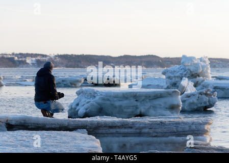 A man kneeling on pack ice on the shore of the St Lawrence at Cap Rouge, Quebec, Canada - Stock Image